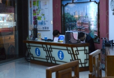 Agents at a tourism agency sit and stare at their phones as they wait for customers.