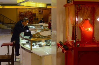 A security guard looks at the diamonds at the rows of jewelry shops that occupy the streets of Yu Garden.
