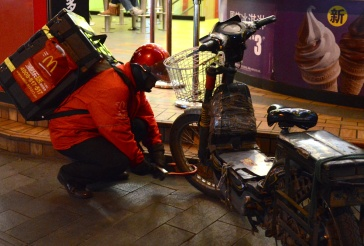A McDonalds delivery man unlocks his rusty, taped-up scooter for his next route.