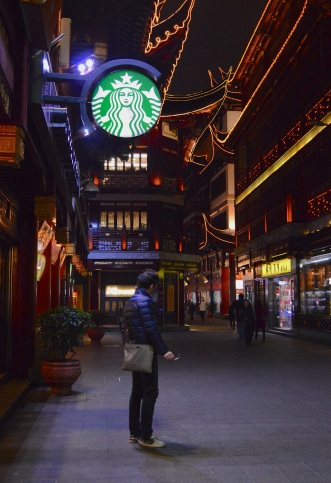A Chinese man smokes a cigarette outside of Starbucks in Yu Garden.