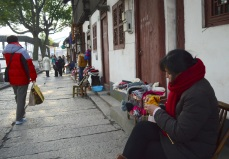 A woman knits as she sits by her sorta pop-up shop on the streets of Zhu Jia Jiao.