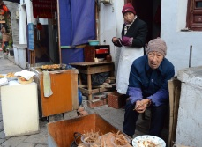 """An old couple selling fried fish asked me to """"help them out"""" as I took this photo."""