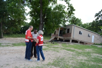 A local deacon and Red Cross volunteers held hands in prayer in front of his church, which was damaged in the recent floods.